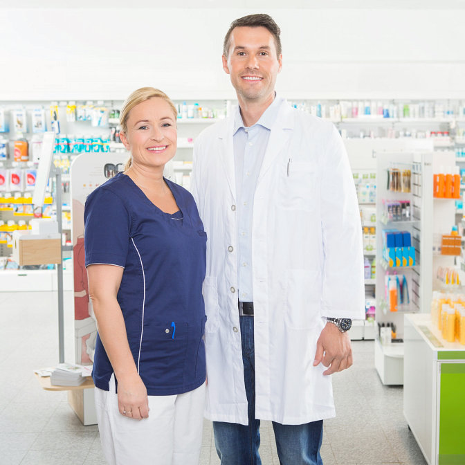 Portrait of confident female assistant and male pharmacist standing in pharmacy