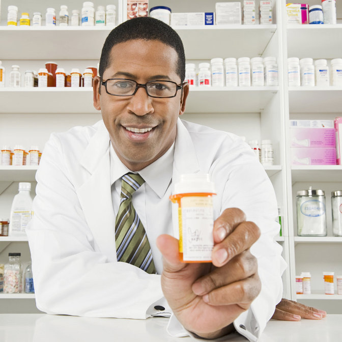 Portrait of a african american pharmacist holding out a medicine bottle
